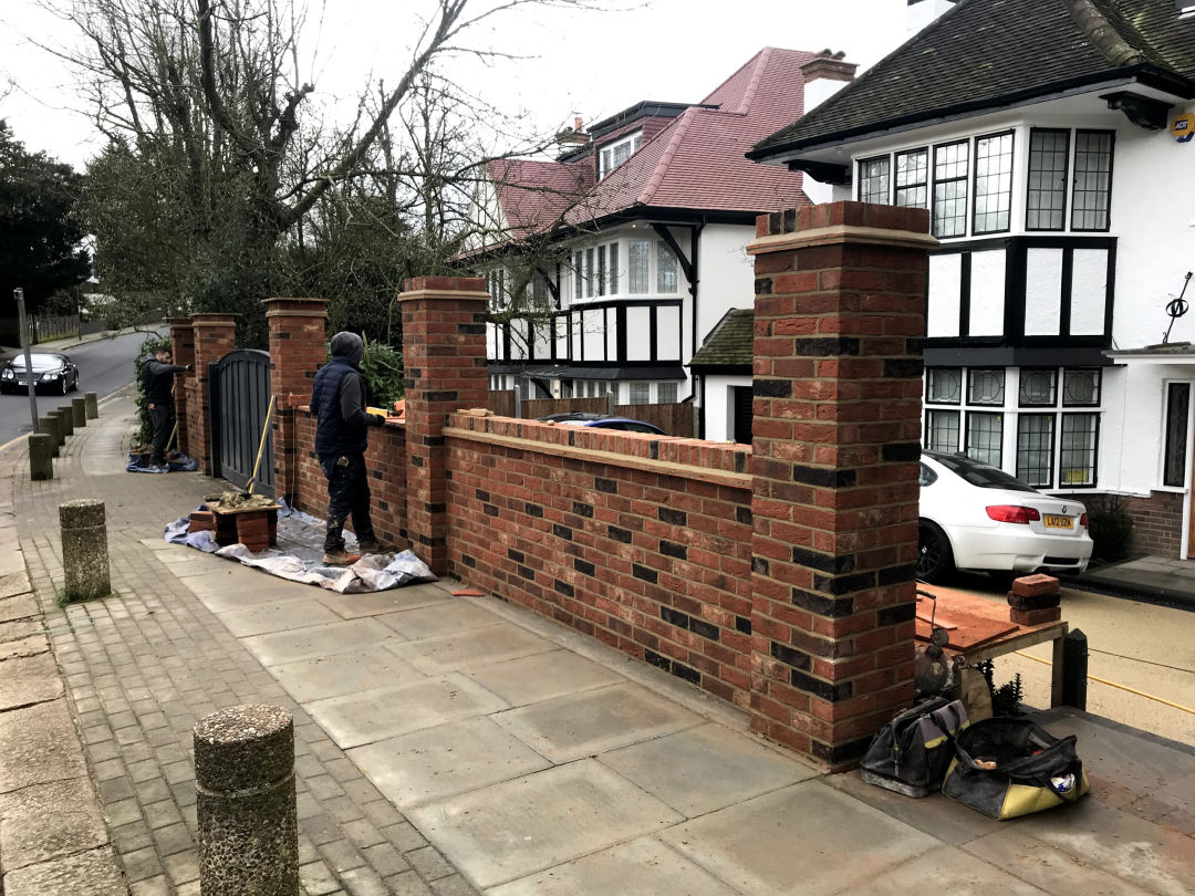 Bricklayers building a brick wall / fence around a London house